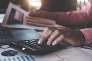 Conceptos de contabilidad contable, hombre usando calculadora para calcular con lápiz y computadora portátil para trabajar financiero y presupuesto, concepto de contador inspector. foto