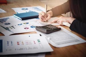 Conceptos de contabilidad de tenedor de libros, bolígrafo de uso femenino, calculadora y cuaderno de trabajo financiero y presupuestario, concepto de contador inspector foto