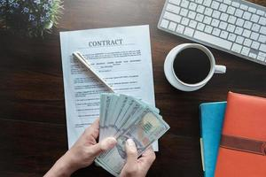 contract and agreement concept, man holding dollar band  and sign contract application paper with coffee cup keyboard and notebook on wood desk in office bank. photo