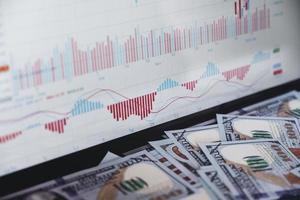 gráfico del mercado de valores en la computadora portátil del monitor y simulación del banco del dólar. foto