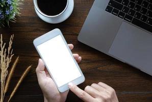 mujer de negocios con smartphone con ordenador portátil en caffee shop. teléfono inteligente o móvil con pantalla en blanco y puede agregar sus textos u otros, concepto de tecnología. foto