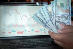 dólar banco simular y gráfico del mercado de valores en el monitor de la computadora portátil. foto