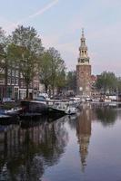 One of the churches of Amsterdam in Netherlands unique with city scene along canal in morning natural light photo