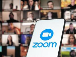 Bucarest, Rumanía 2021- smartphone que inicia la aplicación de reuniones en la nube de zoom con reunión en un monitor de fondo foto