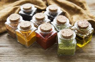 Jars with dried herbs spices on the table photo