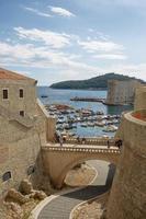 Puerto y turistas vistos a través de las murallas de la fortaleza en Dubrovnik Croaria foto