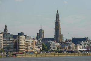 View of a port of Antwerp and cathedral of our lady in Belgium over the river photo