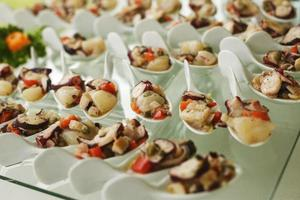 Seafood served on porcelain spoons photo