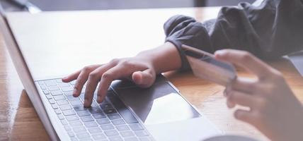 las compras en línea. Mujer asiática escribiendo información de la tarjeta de crédito con el teclado de la computadora portátil para comprar en línea. foto