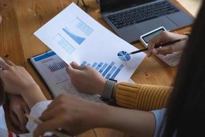 grupo de empresarios de intercambio de ideas, consultor de inversiones que analiza los documentos de balance del informe financiero de la empresa. concepto de administrador de fondos. foto