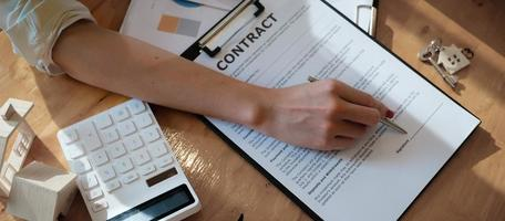 Businesswoman putting signature on a contract at a business meeting with business partners. photo