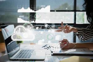 Contador asiático o empresaria apuntando al holograma de la red financiera. foto