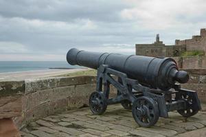 Old Iron Cannon at Bamburgh Castle on Northumberland Coast of England UK photo