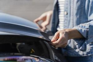 Woman looking at her car to solve a problem photo
