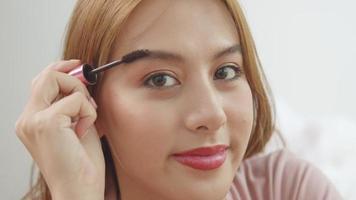 Closeup of a Young Asian Woman Doing Makeup Eyebrow Brush video