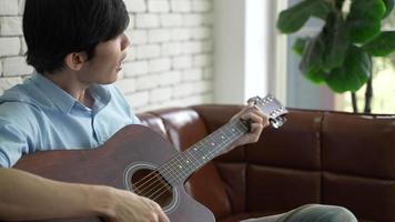 Joven asiático tocando la guitarra y cantando en casa video