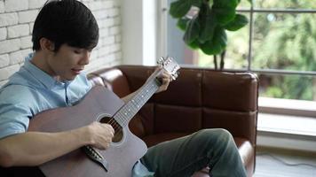 jonge Aziatische man gitaarspelen en zingen thuis video