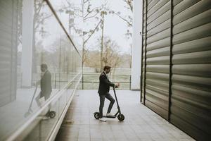 Businessman on a scooter between buildings photo