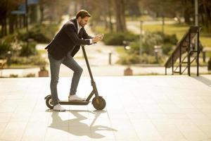 Hombre apoyado en un scooter y mirando su teléfono foto