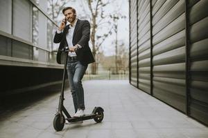 Man holding a scooter and talking on phone photo