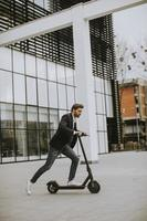Casual businessman riding a scooter to work photo