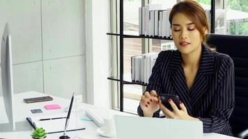 femme d & # 39; affaires travaillant au bureau et à l & # 39; aide d & # 39; un smartphone video