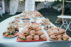 buffet de bodas con varios bocadillos y hamburguesas en la naturaleza foto