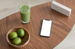Detox juice and smartphone with blank screen on a wooden table photo