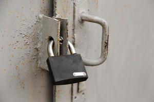 Background of door with lock in metal material and copyspace on wall photo