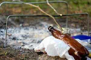 A pile of garbage in the forest park near the campfire site environmental pollution photo