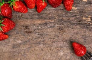 Fresas frescas y una baya en la horquilla bodegón sobre fondo de madera oscura. foto