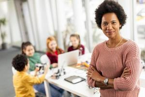Profesora de ciencias afroamericana con un grupo de niños que programan juguetes eléctricos y robots en el aula de robótica foto