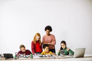 Niños felices con su profesora de ciencias afroamericana que programan juguetes eléctricos y robots en el aula de robótica foto