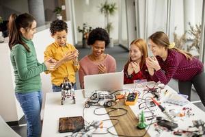 Niños felices con su profesora de ciencias afroamericana con programación de portátiles, juguetes eléctricos y robots en el aula de robótica foto