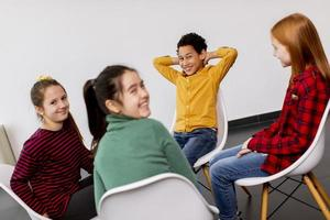 Portrait of cute little kids in jeans  talking and sitting in chairs against white wall photo