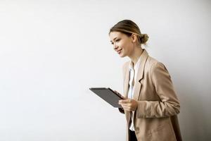 Young woman holding digital tablet by the white wall in modern office photo