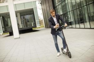 Young businessman using mobile phone on electric scooter photo