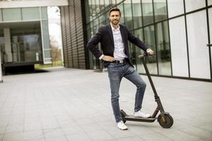 Young business man in a casual clothes standing on electric scooter by an office building on a business meeting photo