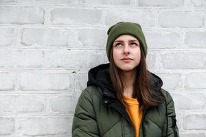 Portrait of a beautiful pensive girl in a yellow sweater and khaki hat photo