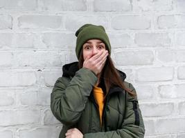 Portrait of a beautiful shocked girl who closes her mouth with her hand in a yellow sweater and khaki hat that stands near a white brick wall photo