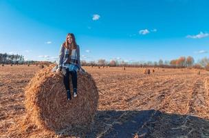 A girl of European appearance in a gray coat stands in a field near a larger bale with hay against a blue sky photo