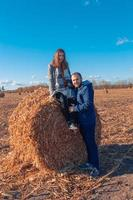 A girl and a guy are standing near a large bale with hay in a field and blue sky photo