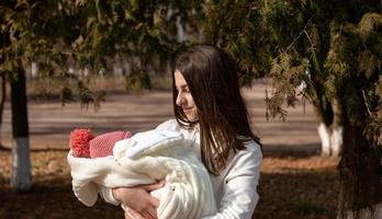 Pretty young woman holding a newborn baby in her arms photo