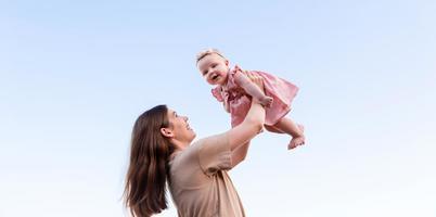 joven madre sostiene a su hija en el aire y riendo en el cielo foto