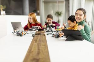 Niños felices programando juguetes eléctricos y robots en el aula de robótica foto