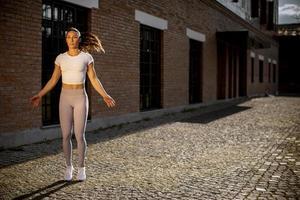 Mujer joven que se extiende durante el entrenamiento en el entorno urbano. foto