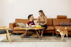 Young woman and young man using laptop for onlin payment while sitting by sofa with their shiba inu dog at home photo