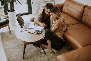 Young woman and young man using laptop while sitting by sofa at home photo