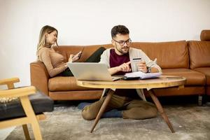 Young woman and young man using laptop for onlin payment while sitting by sofa at home photo