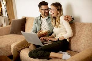 Young couple using laptop together while sitting on sofa at home photo